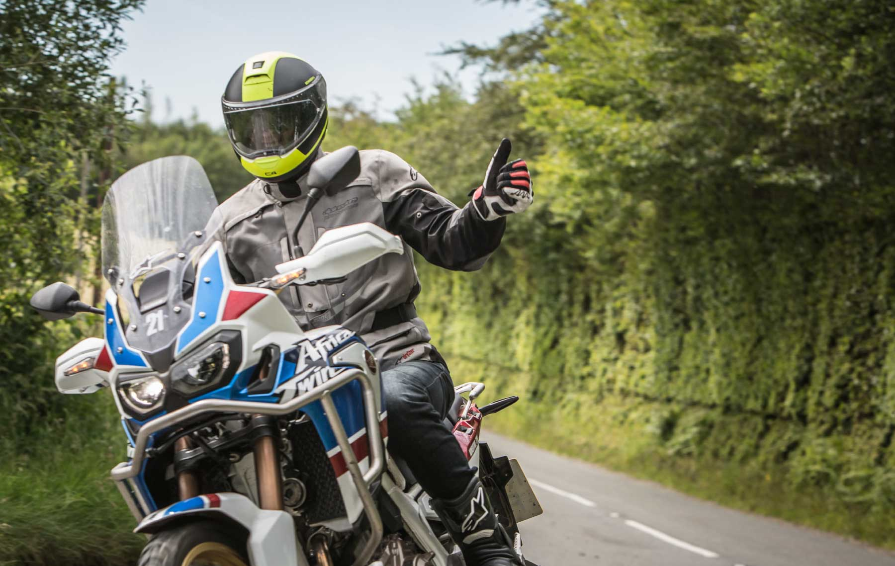 "An man giving a ""thumbs-up "" to the camera onboard Hondas new Africa Twin Motorcycle"